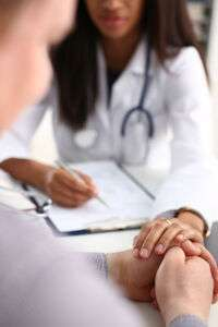Female doctor holding patient hand
